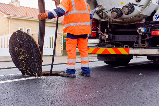 workers cleaning and maintaining the sewers on the roads