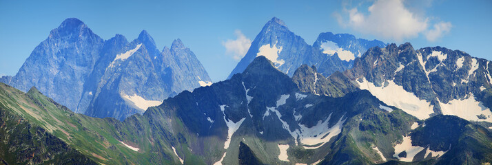 Wall Mural - Panorama Caucasus Mountains. Sharp peaks, snow on the slopes. Traveling in the mountains, climbing.