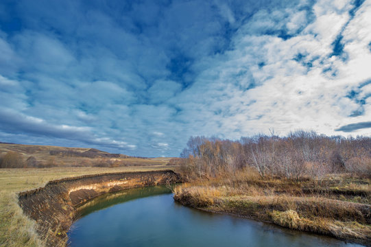 Winter, autumn landscape. The river with ice, trees without leaves, dark sky, withered grass. The earth is waiting for snow, snow drifts.