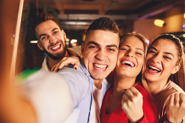 Group of young people having fun in a night out in billiards club and taking selfie