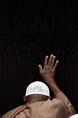Rear view of Muslim man touching Kaaba while praying at al-haram mosque