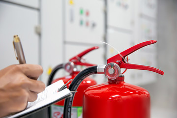Engineers are checking fire extinguishers in the fire control room for prevention.