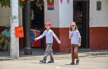kids walking on the street of a village in south america