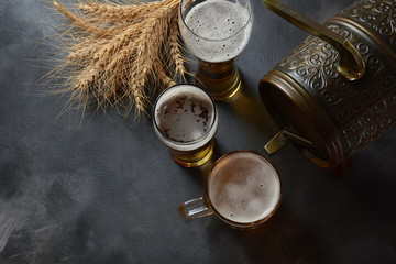 Beer glasses and wheat on dark background