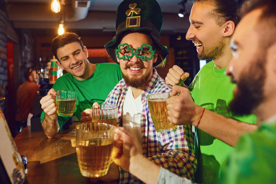 Happy friends celebrating St. Patrick's Day in a bar.