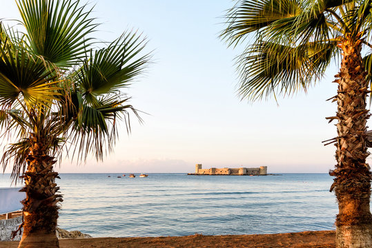 Mersin, Turkey - August 16, 2019: Maiden's castle, Kiz Kalesi with palm in Mediterranean Sea. Mersin Turkey