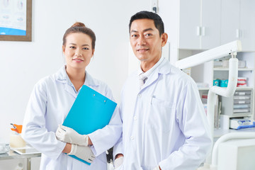 Horizontal medium potrait of dental surgeon and dental assistant wearing white coats looking at camera smiling