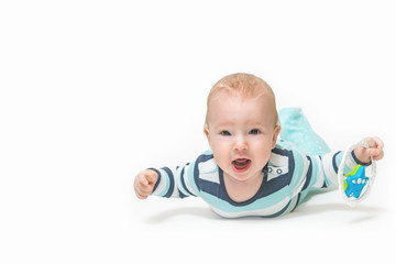 Front view of baby boy lying on white background holding a toy and looking at the camera. Photo contains a lot of free space for your use. All potential trademarks are removed.