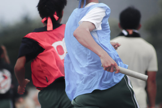 Rear View Of Men Running In Relay Sport