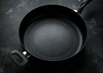 new non-stick aluminium frying pan on dark background