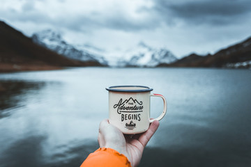 Close-up of male hand holding mug. The adventure begins travel,hiking and camping concept Wall mural