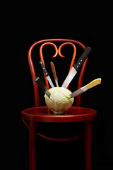 Symbolic conceptual image of a white cabbage on a wooden Thonet chair. Knives are stuck into the vegetable and symbolize cooking, violence, crime, suffering.  On black background.