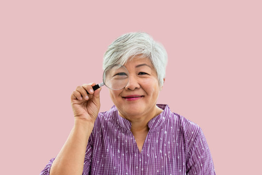 Portrait of senior woman female holding magnifying glass, searching concept, looking at camera