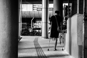 REAR VIEW OF PErson with amputated leg WALKING ON ROAD IN CITY