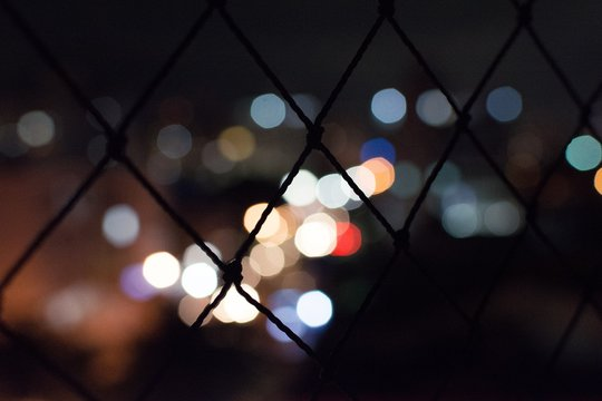 Defocused Image Of Lights Seen Through Chain Link Fence