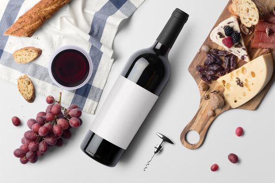 Red wine bottle mockup, on white background, with wine glass, food snacks and blank label to place your design
