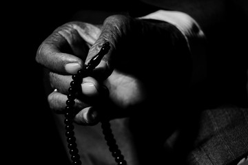 Cropped Hand Of Man Holding Rosary Beads While Praying