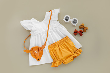 White dress,  orange shorts with kids handbag and sunglasses. Set of  baby clothes and accessories for spring or summer on beige background. Fashion childs outfit. Flat lay, top view