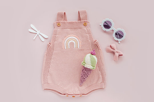 Pink knitted bodysuit with toy ice cream and sunglasses. Set of baby clothes and accessories summer. Fashion newborn. Flat lay, top view