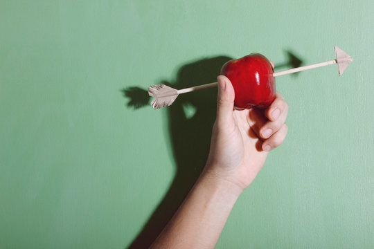 Cropped Image Of Men Holding Apple With Arrow Against Green Background