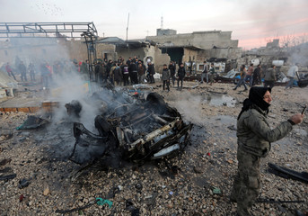 A man takes a picture near a burnt car at the site of a truck blast in Azaz