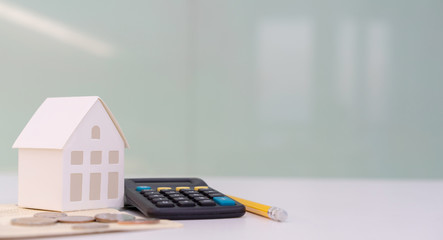 close up house's model on banking account book with calculator, coin and pencil on table for planning of home loan mortgage refinance or retention interest rates , business and financial concept