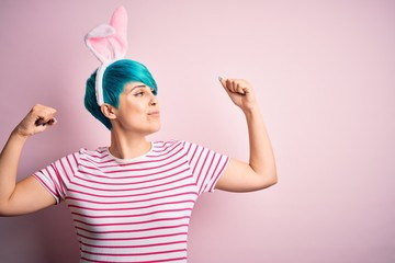 Young woman with fashion blue hair wearing easter rabbit ears over pink background showing arms muscles smiling proud. Fitness concept.