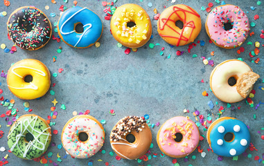 Festive carnival or birthday frame from various colourful donuts