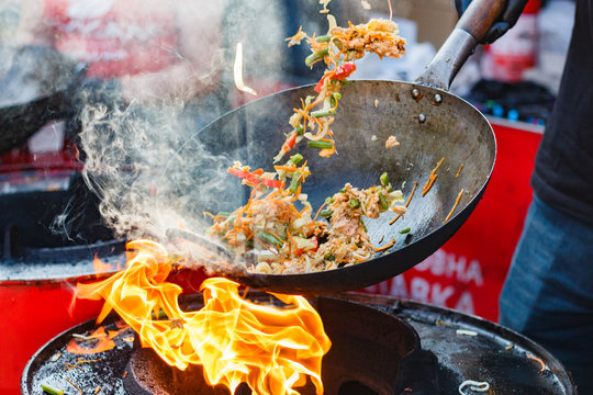 chef cooks Chinese noodle wok at street food festival