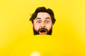 surprised bearded man looking at camera while peeking out from above yellow balloon on yellow background, concept positive emotions