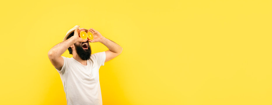 bearded hipster man holding lemon slices in front of eyes, over yellow background, panoramic mock-up with space for text