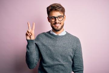 Fototapeta Young handsome man with beard wearing glasses and sweater standing over pink background showing and pointing up with fingers number two while smiling confident and happy. obraz