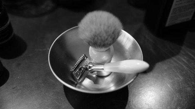 CLOSE-UP OF razor and shaving brush
