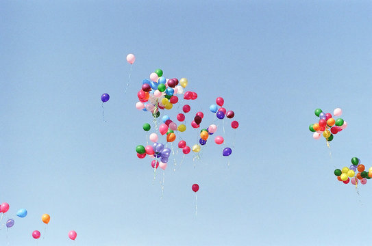 MULTI COLORED BALLOONS AGAINST SKY