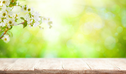 Wooden table and blurred green spring or summer background with flower blossom tree branches. Wall mural
