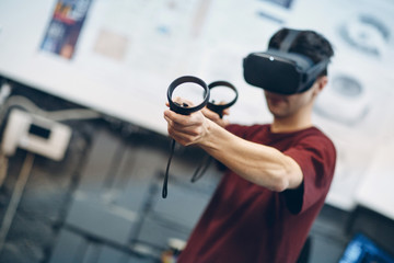 Young man in virtual reality goggles, vr glasses headset with joystick