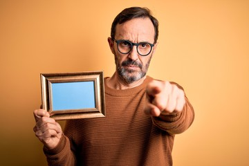 Middle age hoary man wearing glasses holding vintage frame over isolated yellow background pointing with finger to the camera and to you, hand sign, positive and confident gesture from the front