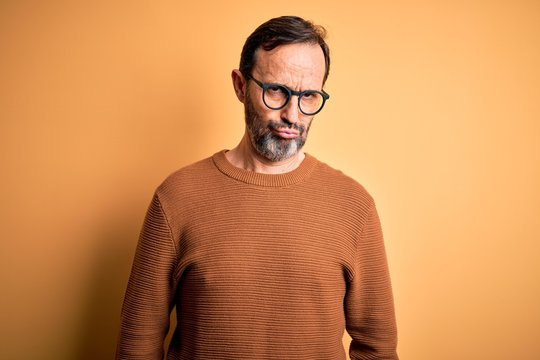 Middle age hoary man wearing brown sweater and glasses over isolated yellow background depressed and worry for distress, crying angry and afraid. Sad expression.
