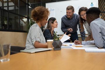 In de dag Hoogte schaal Multiethnic businesspeople brainstorm discussing ideas at team briefing