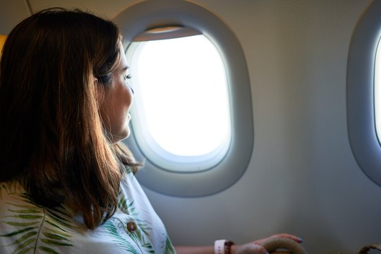 Young traveller woman sitting inside plane at the airport with sky view from the window