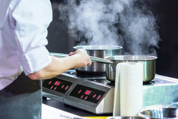 Two ladles for boiling products are on the stove. The chef in the restaurant prepares the ordered dish. Tableware for cafes with non-heating handles. Equipment for restaurants. Culinary master class.