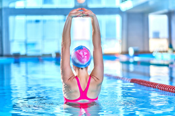 Fit active woman doing water gymnastics and aerobics in a sports swimming pool in leisure center. Pool workout, treatment and prevention of back and neck disease, healthy back