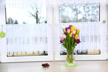 Klorowe tulipany w wazonie na parapecie białego wspłóczesnego okna w jasnej kuchni.