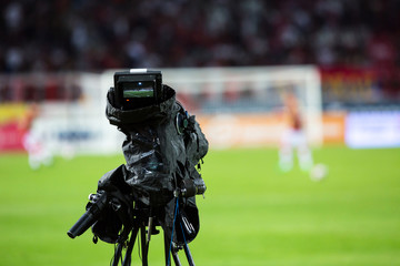 TV camera at the stadium, broadcasting during a football (soccer) match