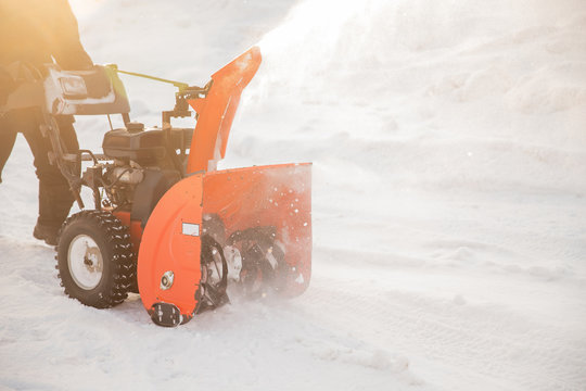 Man cleaning snow from sidewalks with snowblower machine winter
