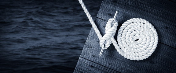 Fotobehang Kikker Boat Rope Secured To Cleat On Wooden Dock With Dark Water Below