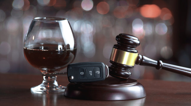 The concept of a DUI. Law hammer, alcohol and car keys on wooden table, dark background