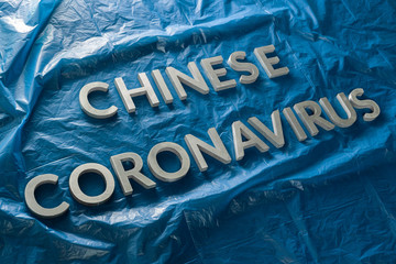The words chinese coronavirus laid with silver metal letters on crumpled blue plastic film - diagonal composition