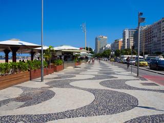 Fotomurales - Copacabana beach with mosaic of sidewalk and kiosks in Rio de Janeiro, Brazil. Copacabana beach is the most famous beach in Rio de Janeiro. Sunny cityscape of Rio de Janeiro