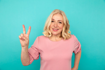 Mid female model showing peace sign and smiling